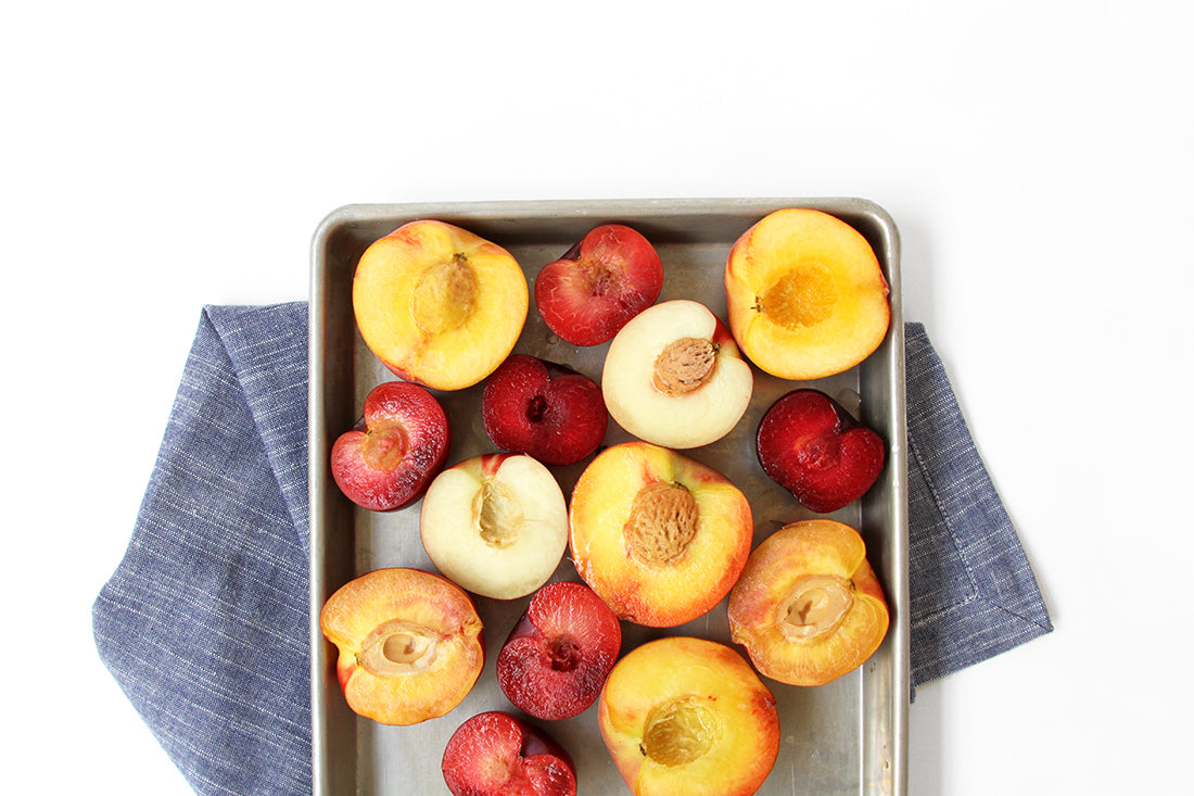 Image from above of halved stone fruits on a baking sheet for Miss Jones Baking Co Stone Fruit Shortcake