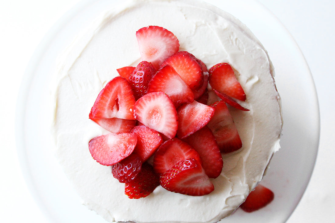 Close up image of top of Miss Jones Baking Co California Strawberry Cake topped with a pile of slices of strawberries.
