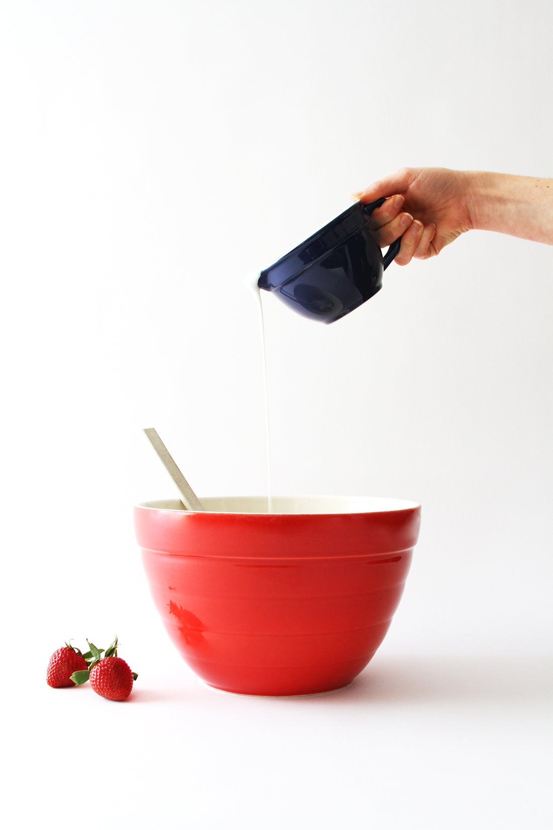 Image of cream poured into red mixing bowl next to two strawberries used for Miss Jones Baking Co California Strawberry Cake