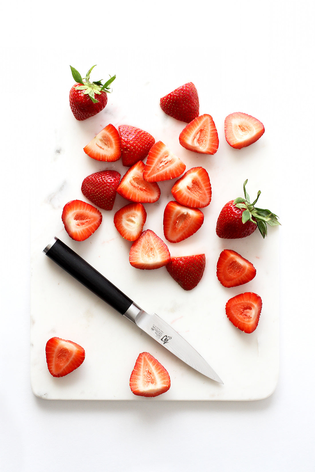 Image of strawberry halves on a cutting board used for Miss Jones Baking Co California Strawberry Cake