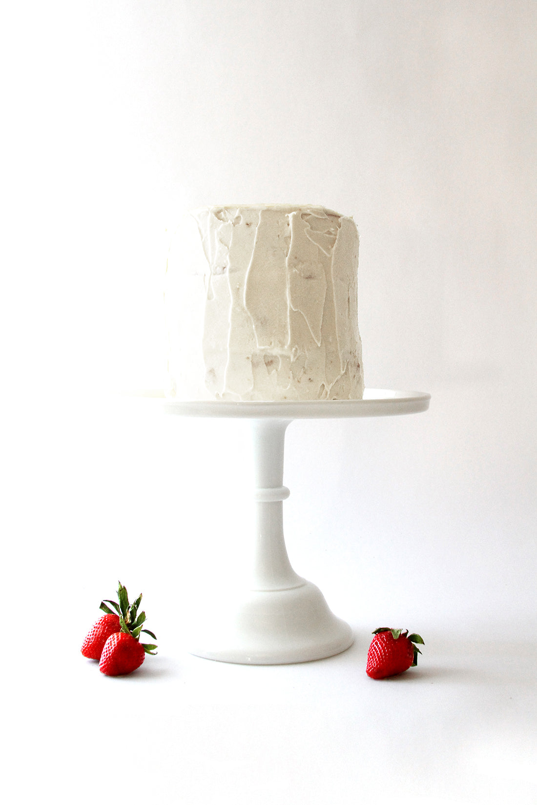 Image of cake stand with Miss Jones California Strawberry Cake on top and three strawberries surrounding the base of the stand.