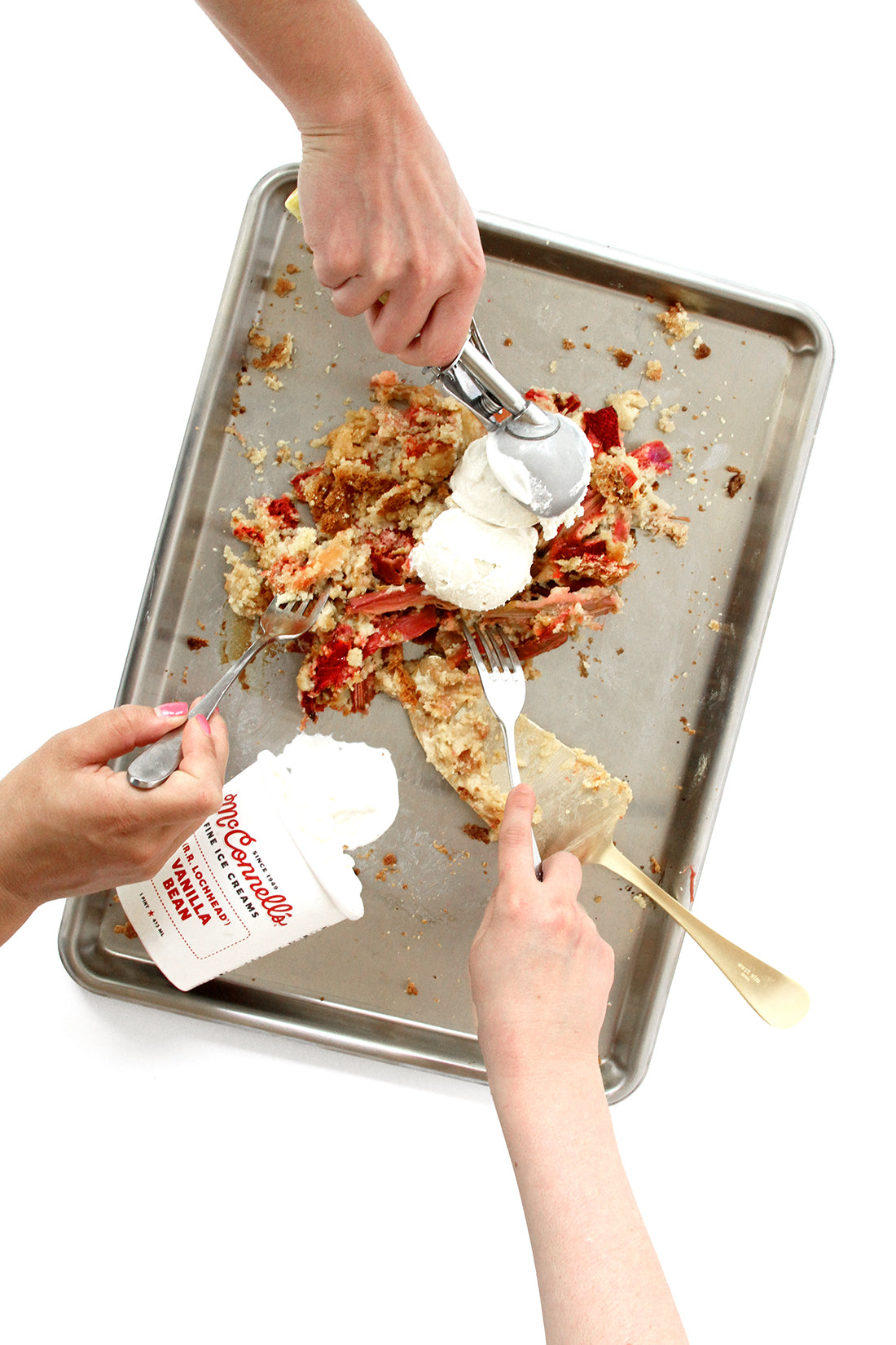 Image from above of crushed Miss Jones Baking Co Summer Strawberry + Rhubarb Tart on a baking sheet next to a container of McConnell's Vanilla Bean Ice cream