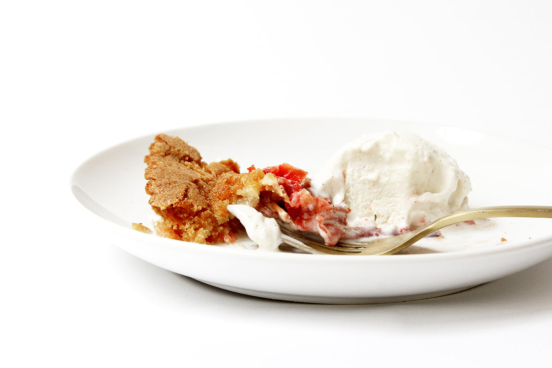 Image of the side of a partly eaten slice of Miss Jones Baking Co Summer Strawberry + Rhubarb Tart next to a scoop of vanilla ice cream and a gold fork