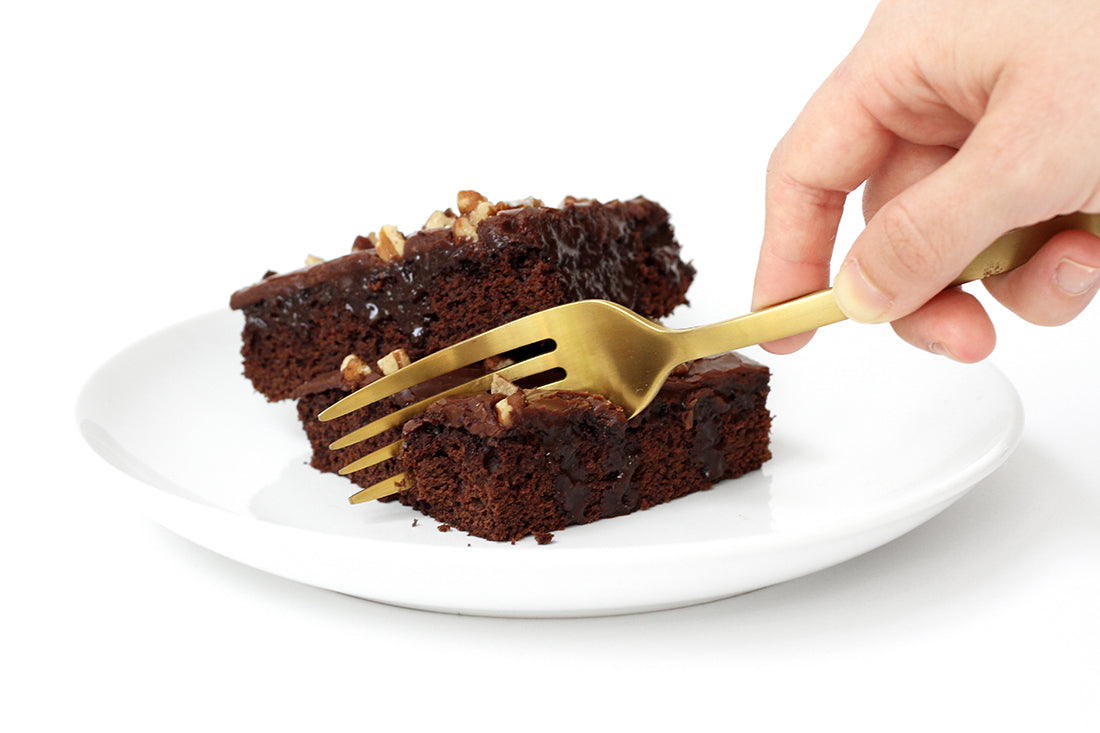 Close up image of two slices of Miss Jones Baking Co Sarah's Texas Sheet Cake on a white plate with a hand taking a bite of one with a gold fork