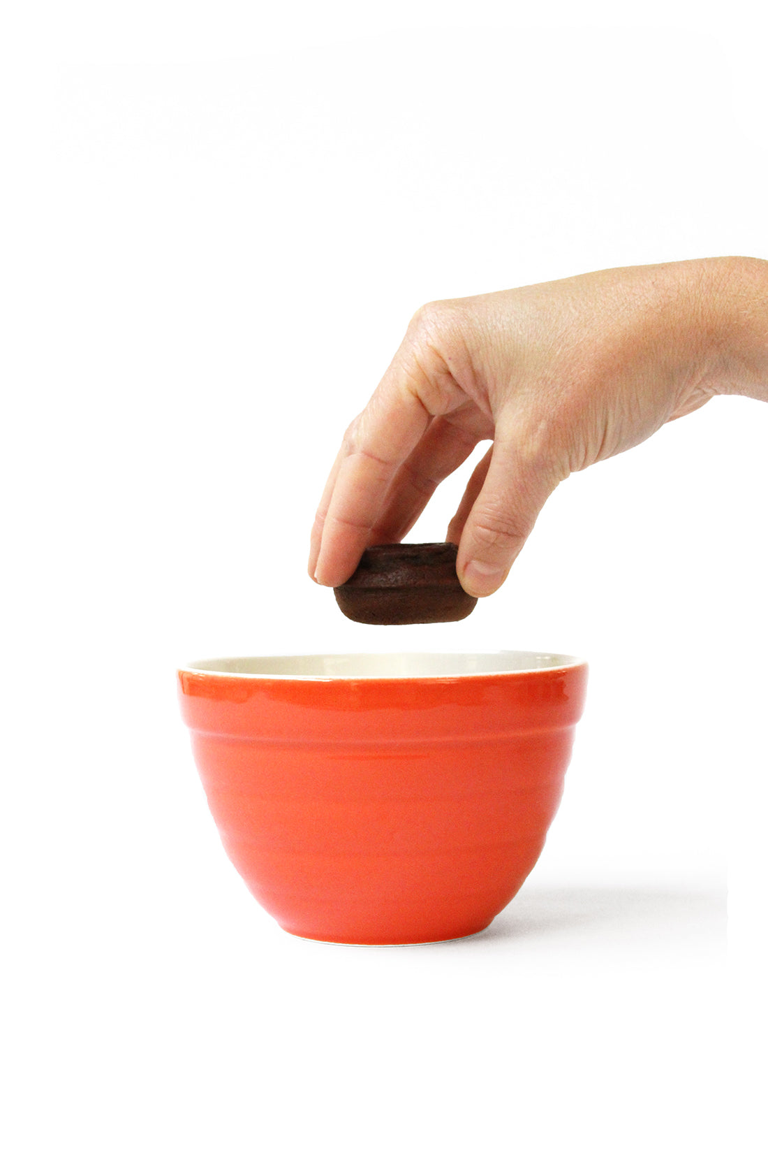 Image of the side of a hand dipping an unfrosted Miss Jones Baking Co Thin Mint Donuts into a red mixing bowl
