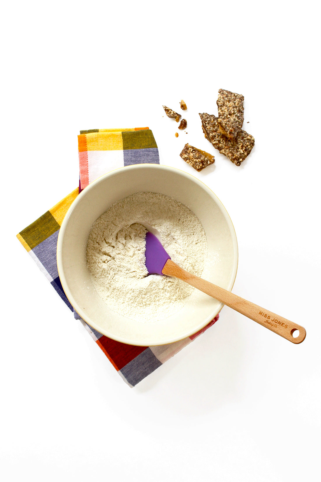 Image from above of Miss Jones Vanilla Cake mix in a mixing bowl next to toffee slices for Miss Jones Baking Co Sarah's Toffeedoodles