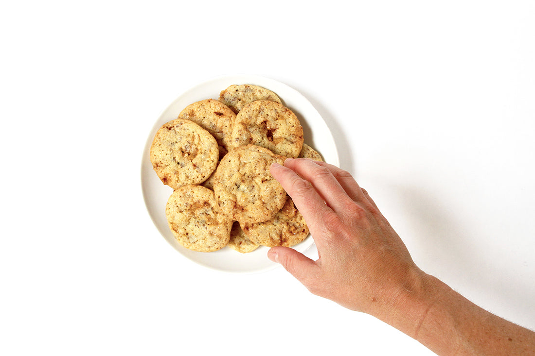 Image from above of a hand grabbing a cookie off of a plate full of Miss Jones Baking Co Sarah's Toffeedoodles