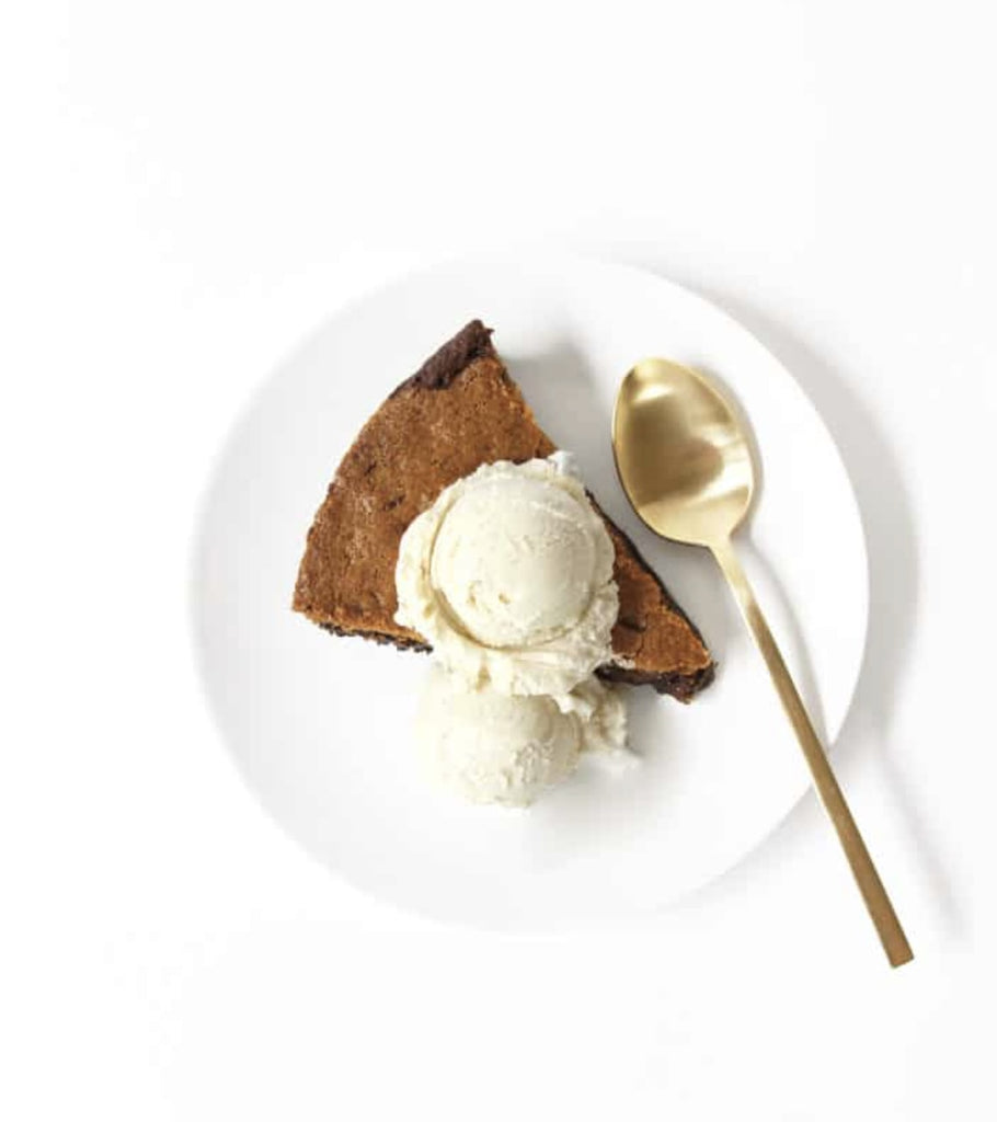 A slice of Miss Jones Chocolate Chip Brownie Skillet on a white plate with a scoop of vanilla ice-cream on top next to spoon