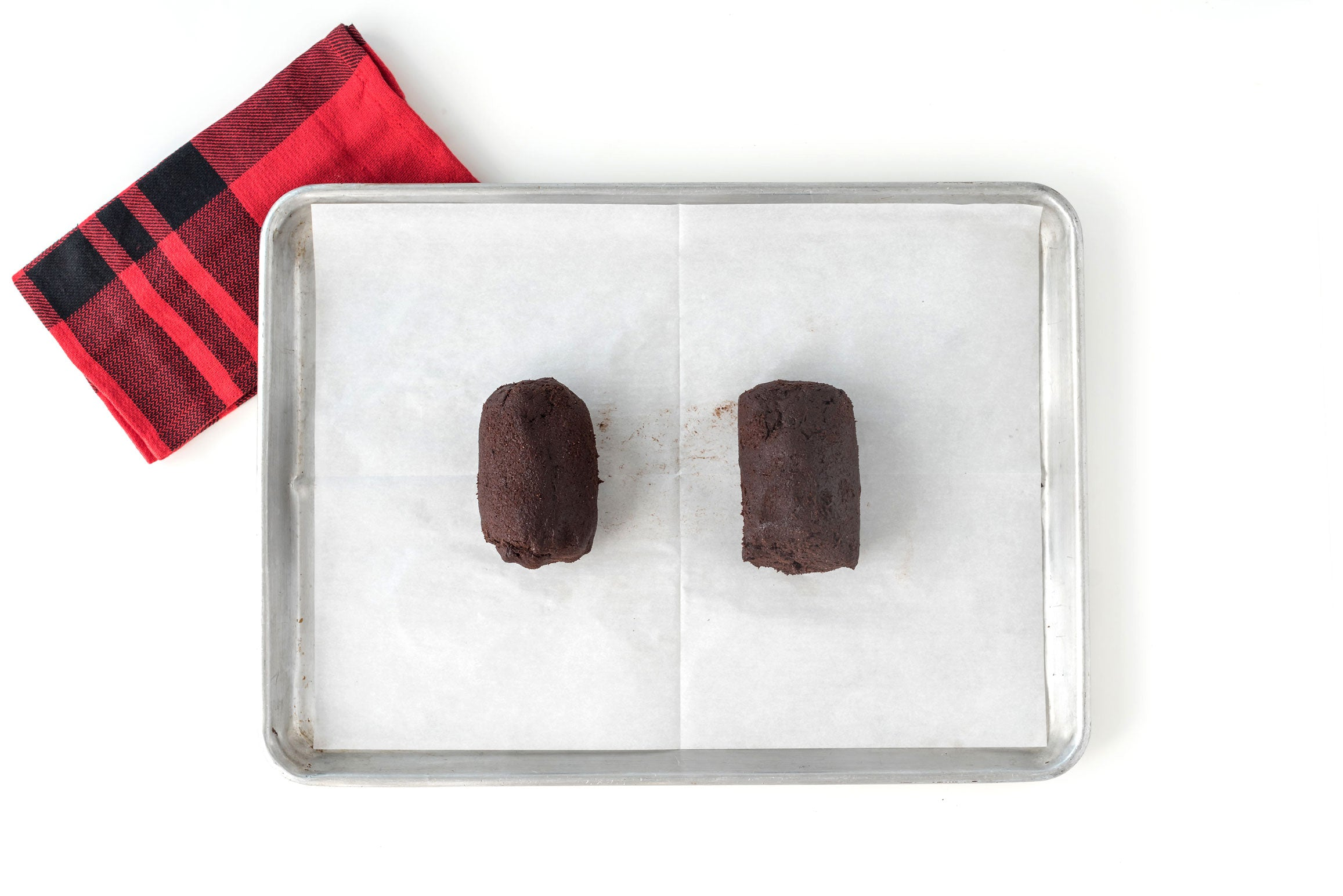 Image of two balls of Miss Jones Baking Co Easy Chocolate Peppermint Cake Mix Biscotti dough on a baking sheet next to a red towel
