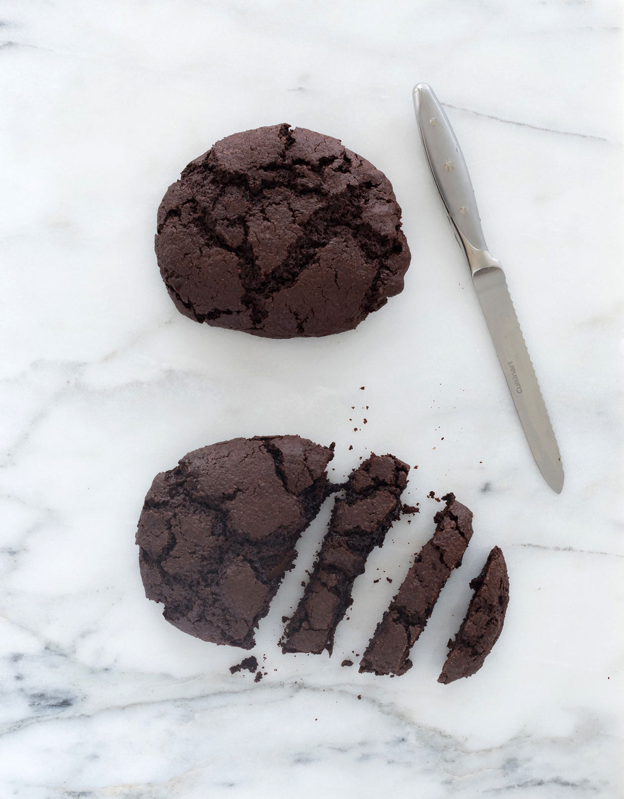 Image of top of two Miss Jones Baking Co Easy Chocolate Peppermint Cake Mix Biscotti cookies, one of which is partially cut into slices, on a marble counter next to a knife