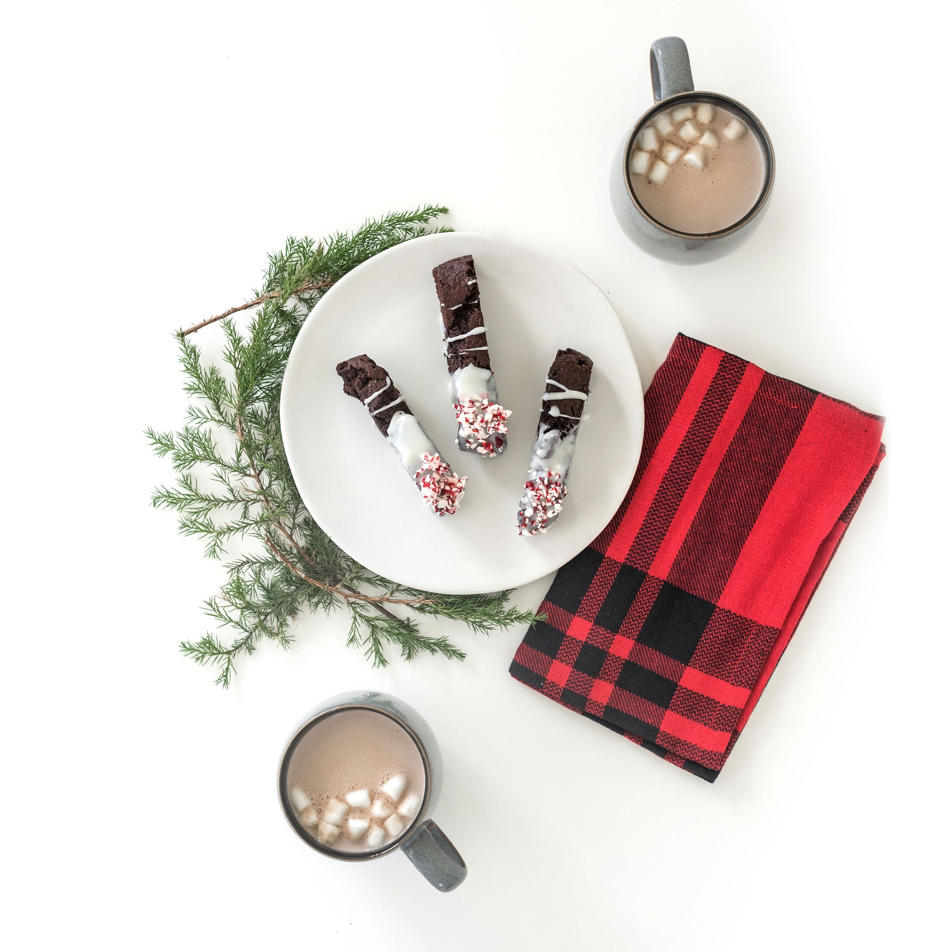 Image from above of three Miss Jones Baking Co Easy Chocolate Peppermint Cake Mix Biscotti cookies on a white plate next to two mugs of hot chocolate with mini marshmallows, a red towel, and a sprig of Christmas tree