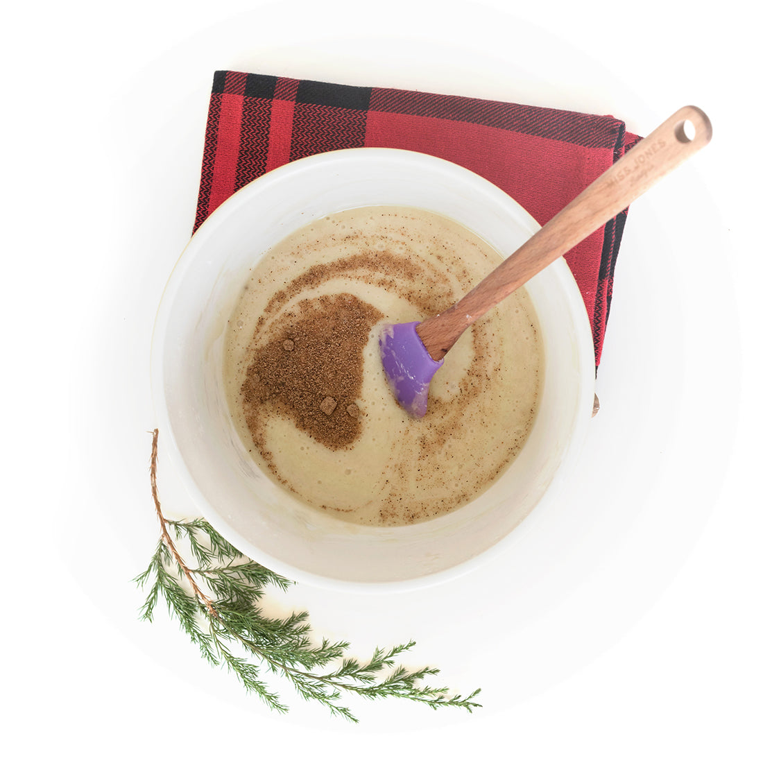 Image from above of Miss Jones Baking Co Easy Holiday Eggnog Mini Donuts batter in a mixing bowl with a purple spatula next to a red towel and a sprig of a conifer branch