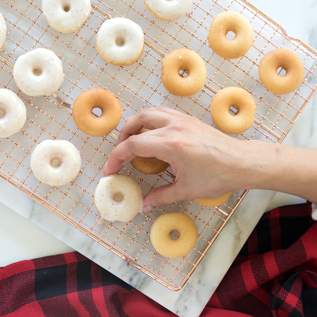 Image of a hand putting down glazed Miss Jones Baking Co Easy Holiday Eggnog Mini Donuts onto a copper baking rack