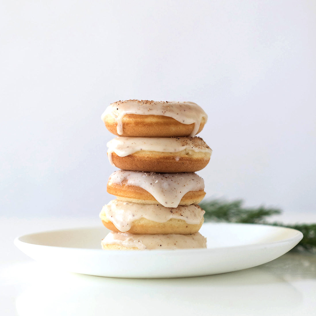 Image of side of five Miss Jones Baking Co Easy Holiday Eggnog Mini Donuts stacked on a white plate