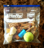 dog treats tennis ball Hefty zippered plastic bag used to organize pet travel.