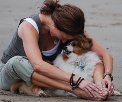 According to Woman with dog on beach. Japanese scientists, humans and dogs bond the same as human mothers and newborns.