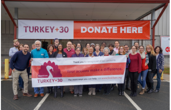 Foodshare team holding turkey donation sign
