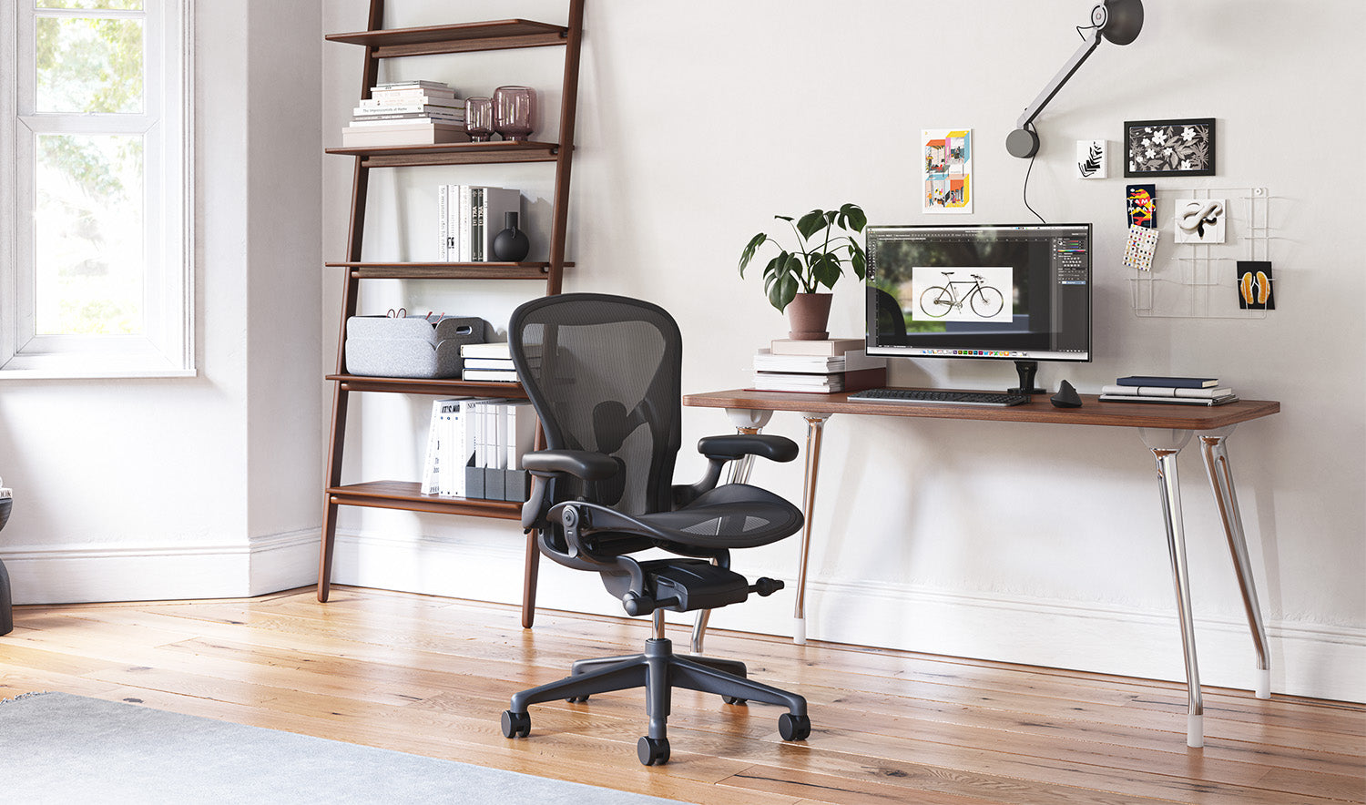 A graphite Aeron chair in front of an AbakEnvironments desk. A Hew side table and Folk shelving unit are against the walls in a home office.