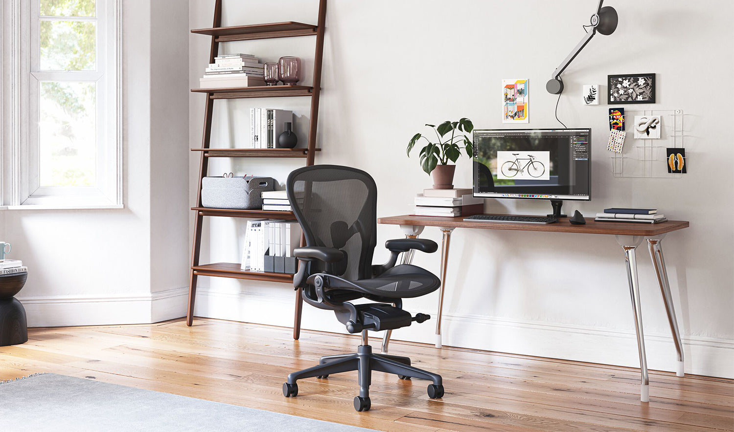 An AbakEnvironments Desk with a walnut top and polished legs, with a graphite Aeron Chair in a light home office setting and Folk Ladder Shelving.