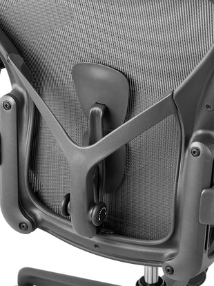 Rear view of a graphite Aeron office chair, showing back support and adjustable arms.