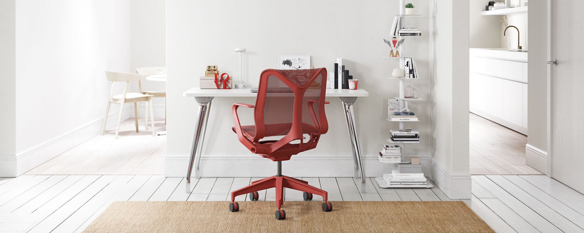A light home office environment featuring a Canyon Red Low Back Cosm Chair against a white AbakEnvironments Desk with a white Lolly Lamp