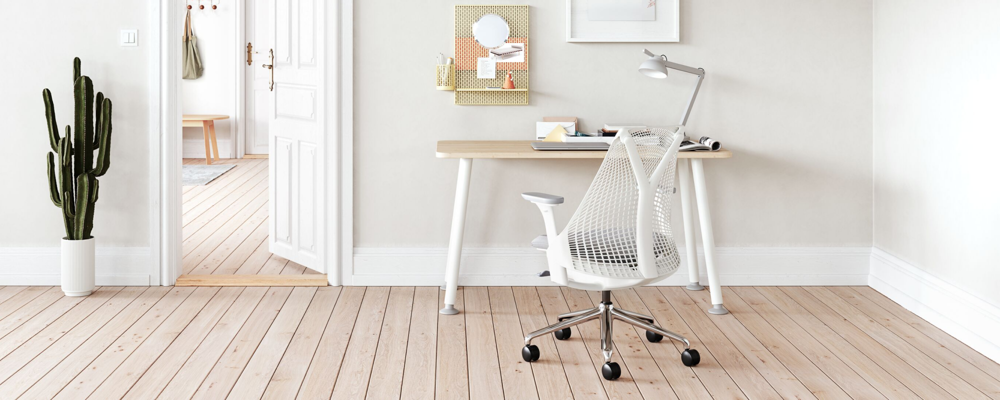 A light home office environment featuring a White Sayl Chair with polished base at a Halifax White Oak Memo Desk with a Formwork Paper Tray ontop