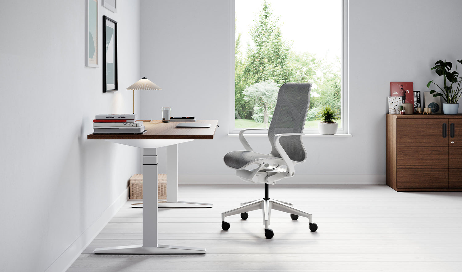 Grey and white Cosm chair next to a Ratio sit stand desk in a home office setting