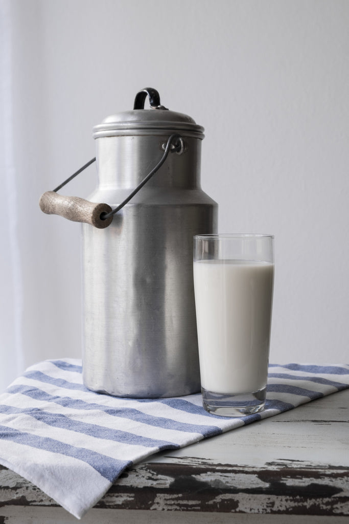 A metal jug of milk on a table, next to a glass of milk.