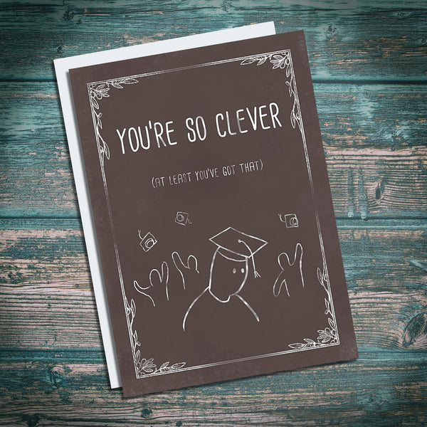 "Cheeky well done, congratulations card. Backhanded compliment, ""you're so clever, at least you've got that""."