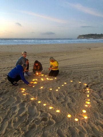 Darkness Into Light candles lit on a beach in Sydney