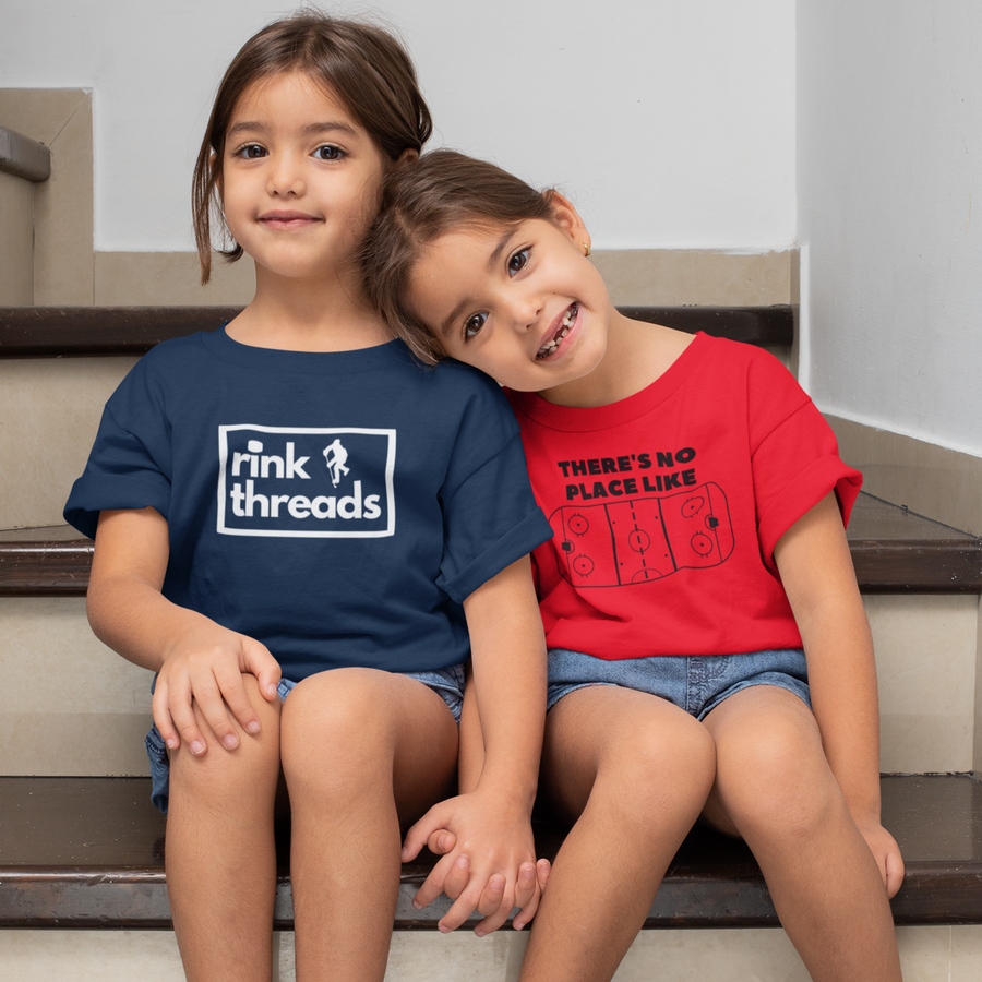 Two twins sitting on the stairs. One is wearing the Rink Threads logo tee in Navy and the other the