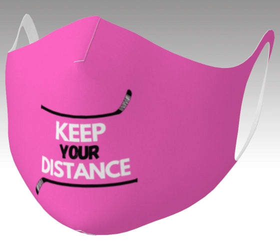 "A mockup of a mask it is pink and says ""Keep your Distance"" in white and black. There is a hockey stick both above and below the words, framing them."