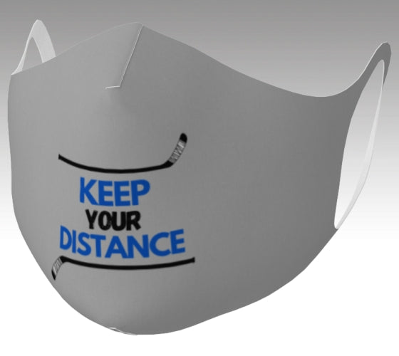 "A mockup of a grey mask that says ""Keep your Distance"" in blue and black. There is a hockey stick both above and below the words, framing them."
