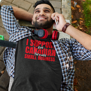 "adu;t man, lying on a park bench on the phone. He is wearing a charcoal grey heathered shirt that says ""I Support Canadian Small Business"" in red and ""Rink Threads"" in white, outlined in black. Rink Threads is superimposed over the red text."