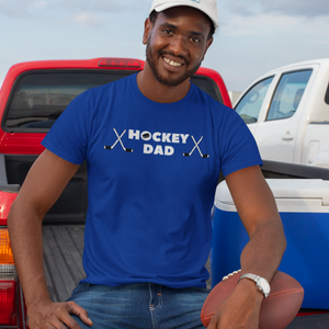 "A man holding a football, sitting on the tailgate of his truck, next to a cooler. He is wearing a royal blue t-shirt with ""Hockey Dad"" written across the chest. There is a puck in the ""O"" of hockey and two crossed sticks on either end."