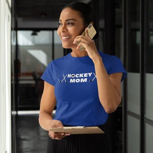 "The same image as the right side of the split screen photo. She is talking on the phone and wearing a royal blue t-shirt with ""Hockey Mom"" written across the chest. There is a puck in the ""O"" of hockey and two crossed sticks on either end"