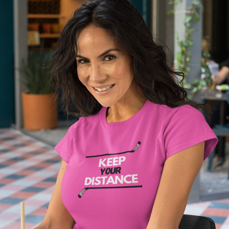 "An adult smiling at the camera. She is wearing a pink t-shirt that says ""Keep your Distance"" in white and black. There is a hockey stick both above and below the words, framing them."