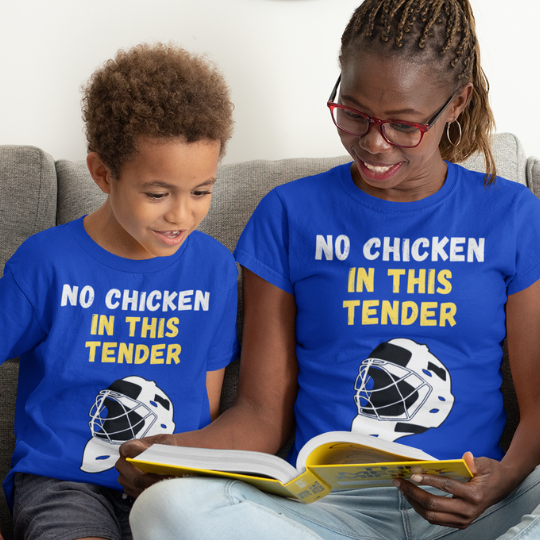 "An adult and a child reading on the couch. They are each wearing  a blue t-shirt that says ""No Chicken in this Tender"" in white and yellow. There is a graphic of a hockey goalie mask in white and black underneath the words."