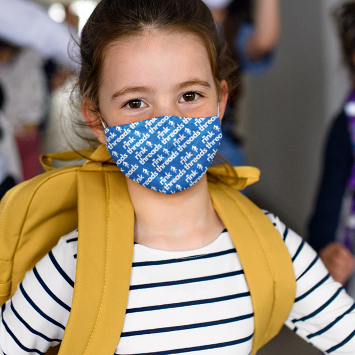 A girl wearing a backpack and a blue mask with the white rink threads logo in a repeating pattern all over it.