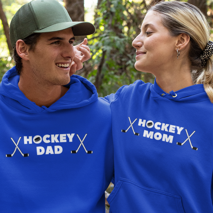 "A young couple in the woods, each wearing a royal blue hoodie. His reads ""Hockey Dad"" written across the chest. There is a puck in the ""O"" of hockey and two crossed sticks on either end. She is wearing the same hoodie but instead of ""Hockey Dad"", it reads ""Hockey Mom""."
