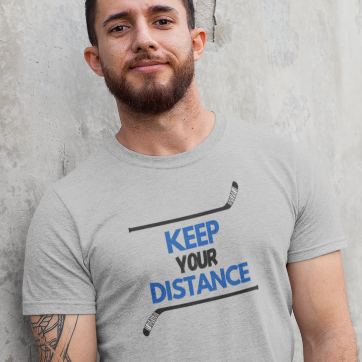 "An adult, giving a half smile, leaning against a wall. He is wearing a sport grey t-shirt that says ""Keep your Distance"" in blue and black. There is a hockey stick both above and below the words, framing them."