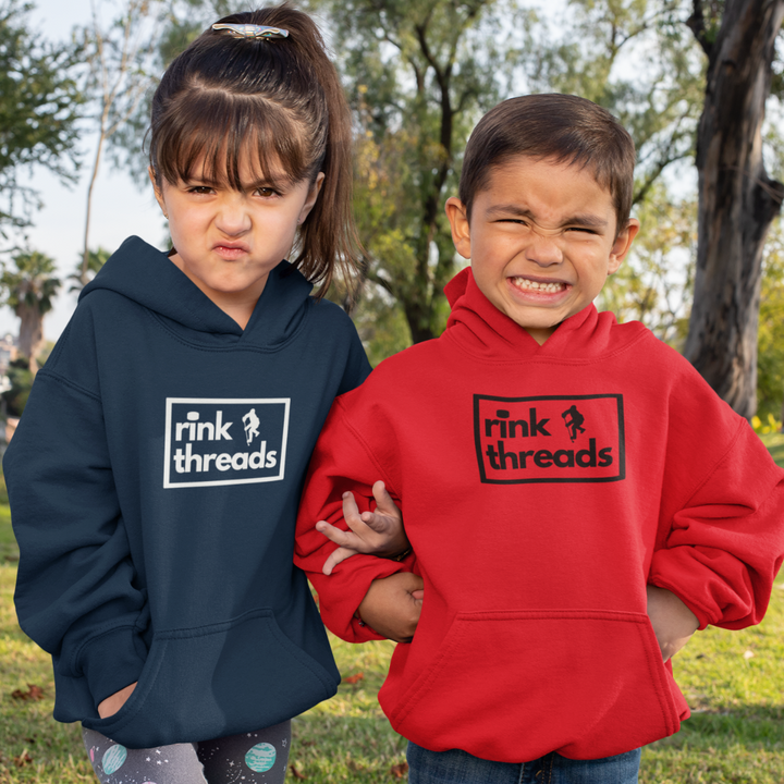 "Two kids making faces, standing in front of trees. They are both wearing hoodies with the rink threads logo in the middle. The rink threads logo is a box with the words ""Rink Threads"" inside. The dot for the I is a puck and there is a hockey player on the right hand side of the logo.. The hoodie on the left is navy, the one on the right is red."