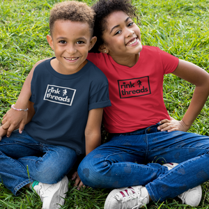 "Two kids sitting on the grass, one's arm around they other. They are both smiling. The one on the left is wearing a navy t-shirt with the rink threads logo in the middle. The rink threads logo is a box with the words ""Rink Threads"" inside. The dot for the I is a puck and there is a hockey player on the right hand side of the logo. The one on the right is wearing a red t-shirt with the Rink Threads logo on it."