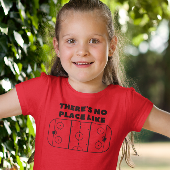 "A child smiling in front of a tree, wearing a red t-shirt with the words ""There's no place like"" in black, above a white graphic of a rink."