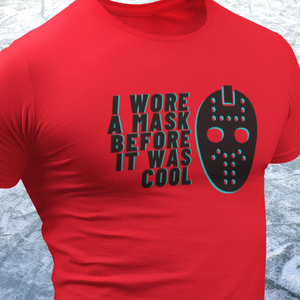 "Mockup of a red shirt that says ""I Wore a Mask Before it was Cool""and a graphic of a vintage goalie mask is on the left, both in black and shadowed with teal."
