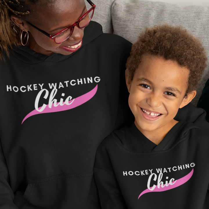 "A woman and a small boy, both wearing black hoodies that read ""Hockey Watching Chic"" in white with a pink brush stroke underneath."