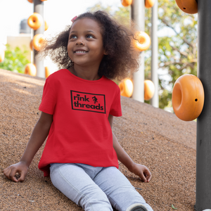 "A child sitting on the playground, wearing a a red t-shirt with the rink threads logo in the middle. The rink threads logo is a box with the words ""Rink Threads"" inside. The dot for the I is a puck and there is a hockey player on the right hand side of the logo."