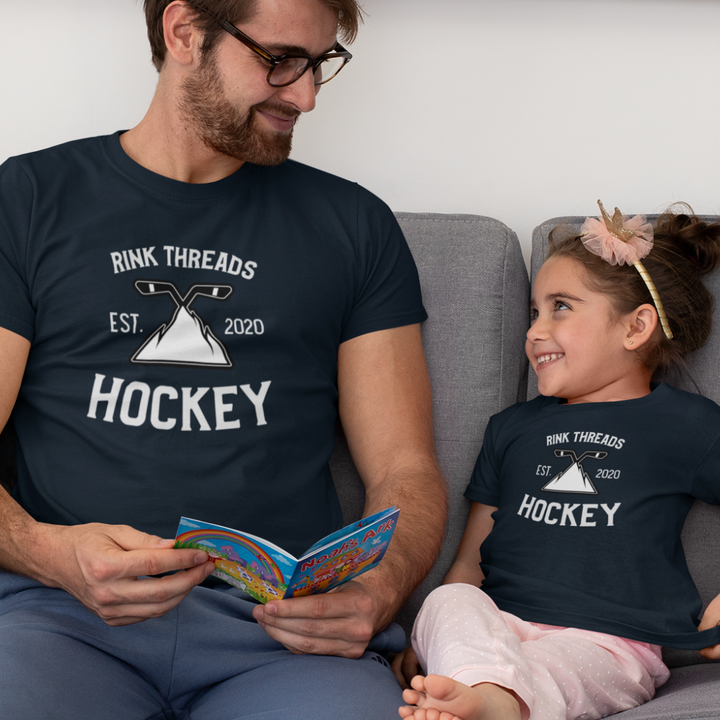 "An adult reading a book to a child on the couch. They are each wearing a navy t-shirt that says ""Rink Threads Hockey Est. 2020"" in white with a mountain who's peak is two crossed hockey sticks in white and black in the middle of the shirt."