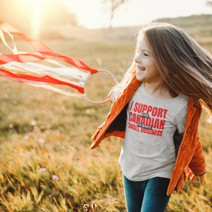 "A child outside, playing with a streamer. she is wearing a sport grey shirt that says ""I Support Canadian Small Business"" in red and ""Rink Threads"" in white, outlined in black. Rink Threads is superimposed over the red text."