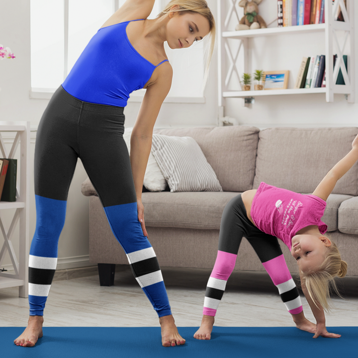 "Adult woman in a blue tanktop and leggings. The leggings have a graphic that look like black hockey pants and blue hockey socks with two white stripes and a black stripe between them. Next to her is a little girl in a pink ""Sugar and Spice"" tee also wearing leggings. her leggings graphic that look like black hockey pants and pink hockey socks with two white stripes and a black stripe between them. They are both doing yoga."